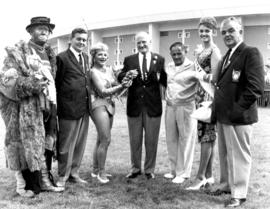 Group photograph of W.J. Borrie, P.N.E. directors, Miss P.N.E., and performers in front of Agrodome