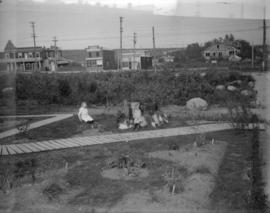 [Jean and Jack Davidson playing in yard at 2119 West 42nd Avenue]