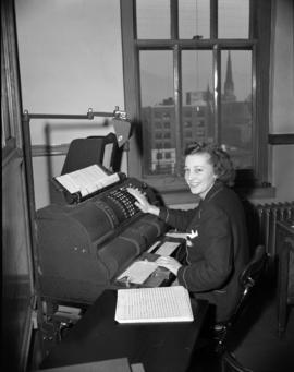 [B.C. Telephone employee using a large adding machine]