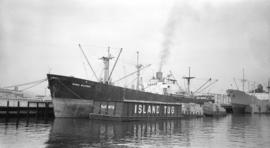 S.S. Maria Delores [at dock, with lumber-filled barges alongside]