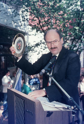 Mike Harcourt holding decorative plate during the reenactment of the first city council meeting a...