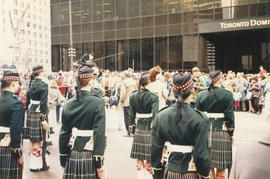 Group of men in kilts in front of Toronto Dominion Bank building during Castle Vancouver opening