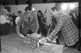 Michael Francis and Mike Harcourt dressed in Centennial tartan placing haggis on table