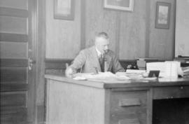 [James Crookall at desk in office at Union Steamship office]