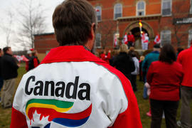 Day 26 A man cheers the flame wearing Calgary 1988 Olympic Jacket in Hampton, New Brunswick.