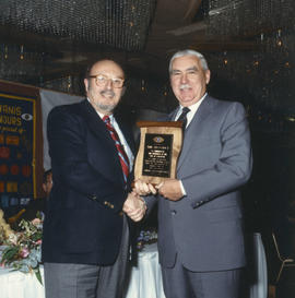 Robert Gordon Rogers delivering plaque to man at Kiwanis Club Centennial luncheon