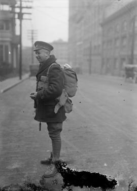 [Soldier with pack and gear in the street]