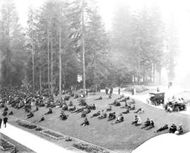 Stanley Park, visitors seated on the grass near Pavilion and Bandstand