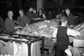 [Employees sorting Christmas parcels at the post office]