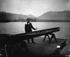 [Man beside canoe on a dock]