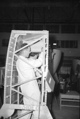 [Man assembling airplane at Boeing plant on Sea Island]