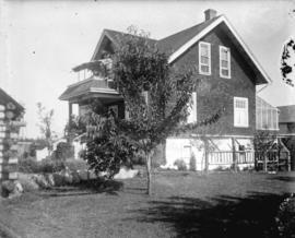 [Rear view of house, showing lawn and tree]