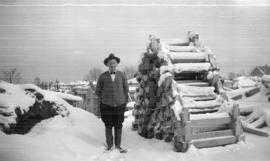 [Job no. 580 : photograph of man by wood pile at Vancouver City Hall construction site]