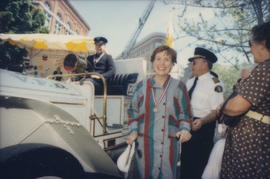Unidentified woman beside V.P.D. vehicle