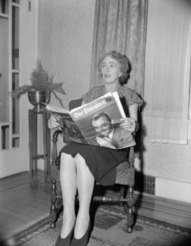"[Woman reading ""The Standard"" newspaper]"