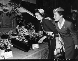 Miss P.N.E. and model dressed as stewardess with Flowers by Air exhibit in horticultural show, P....