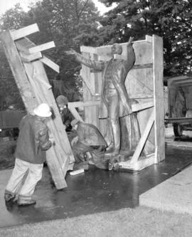 [Parks Board workmen unloading the Lord Stanley statue from a crate]