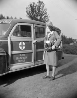 [Red Cross worker carrying bottles of blood to a blood transfusion service vehicle]