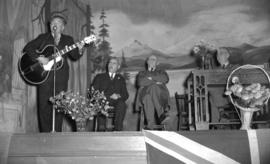 [Man playing a guitar on stage during the 1941 Provincial election campaign]