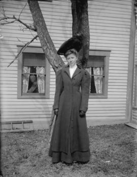[Woman standing in front of tree in coat and hat]