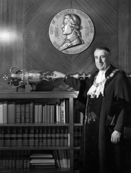 Portrait of Vancouver Mayor F.J. Hume standing beside city mace