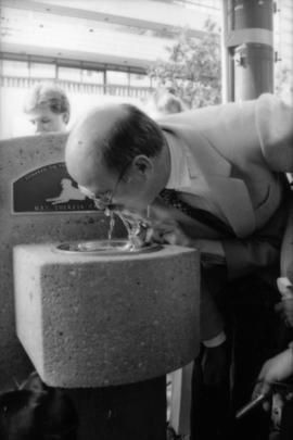 Mike Harcourt drinking from fountain