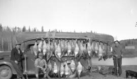 [Hunters standing with] geese [hung] on a canoe