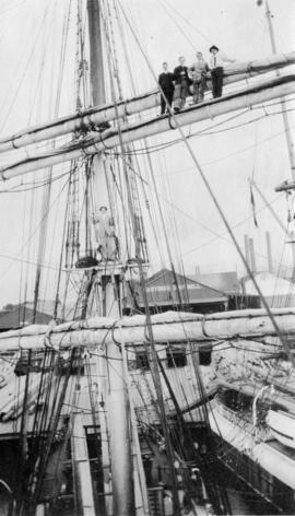 [Men standing on the mast of a tallship at Hastings Sawmill]