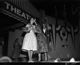 Carol Lucas, winner of Miss P.N.E. 1957, congratulated by the previous year's winner, Joan G...