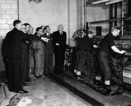 Group of men watching a demonstration of rug carpet cleaning with the Mirza washing machine at Ne...