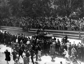 [King George VI and Queen Elizabeth being driven through a crowd-lined road]