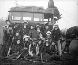[Group of women with field hockey sticks assembled in front of Hotel Vancouver's horsedrawn ...
