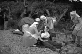 [Nurses bandaging patients at an A.R.P. display]