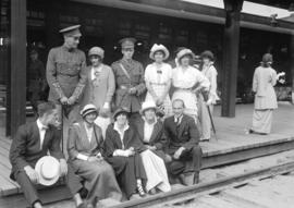 [Two soldiers with civilian friends/relatives at railway platform]