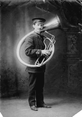 [Full length studio portrait of Philip T. Timms in band uniform with helicon]