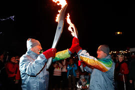 Torchbearer 7 Walter Brodowski (L) passes the flame to Torchbearer 8 Christopher Harding in Maple...