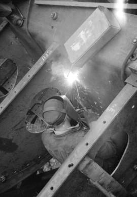 [Welder at work on boat in Burrard Drydocks]