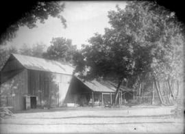 [Farm buildings with carriages stored beside the building under cover]
