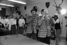Michael Francis and Mike Harcourt dressed in Centennial tartan carrying the haggis
