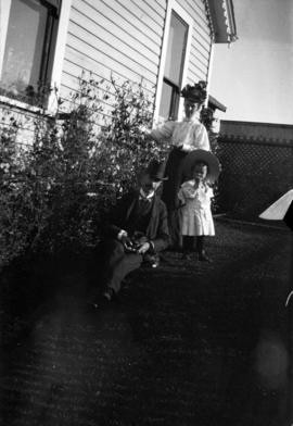[L.D., Annie and Theodore Taylor in yard of home at Willow Street and 8th Avenue in Fairview]