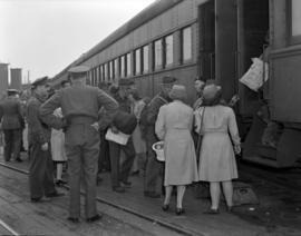 [Red Cross workers distributing fruit to Royal Canadian Army Services Corps men as they board a t...