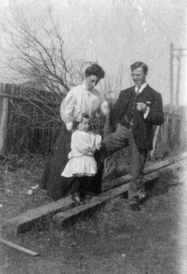 [Unidentified woman, man and girl standing outside]