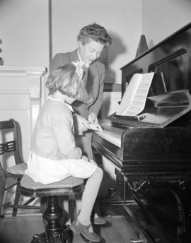 [Woman teaching a young girl to play the piano]