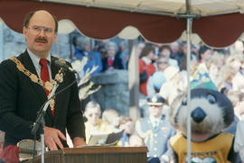 Mayor Harcourt delivering speech with Tillicum in background