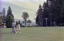 Group walking across field in front of totem poles at Stanley Park