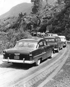[Cars stopped on gravel road during construction of the new Squamish Highway]