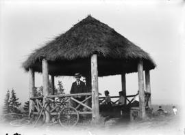 [Men and women in thatched roof gazebo at Prospect Point]