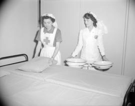 [Red Cross workers making a bed for a blood donor clinic]