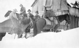[Group of men and horses in front of cabin in snow]