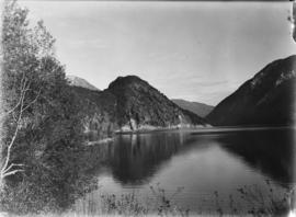 [View of slopes across a lake]